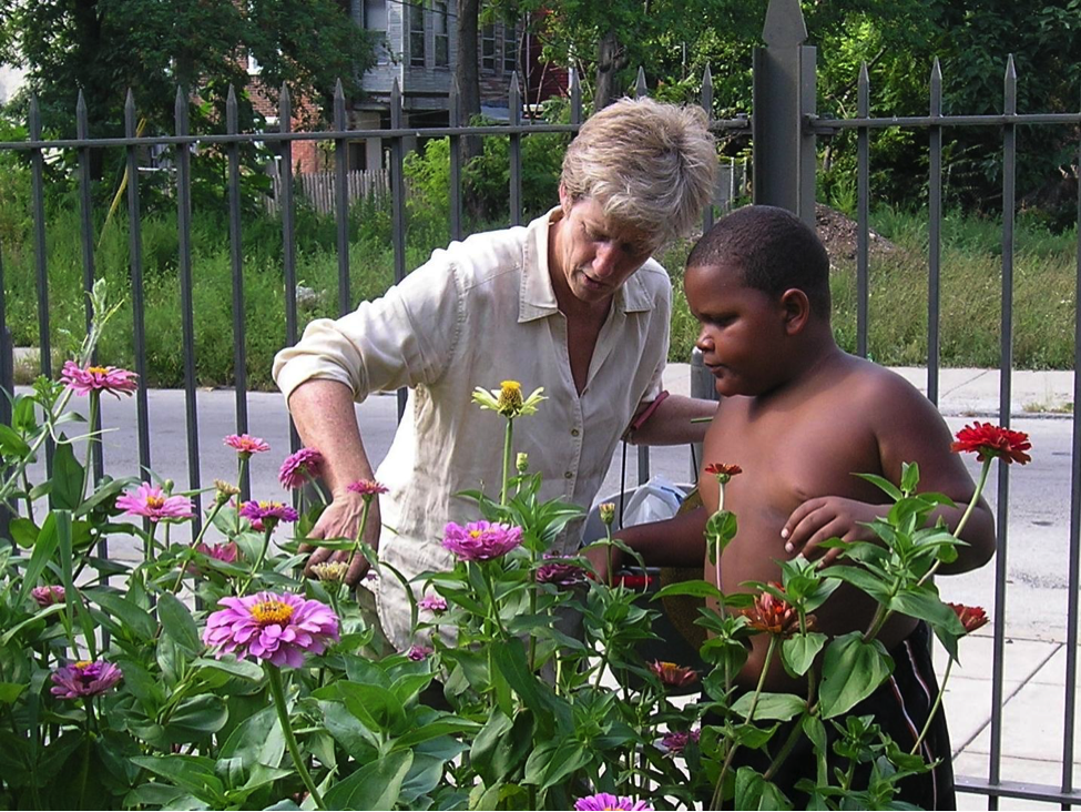 Early Board member Signe Wilkinson gardening with a young boy