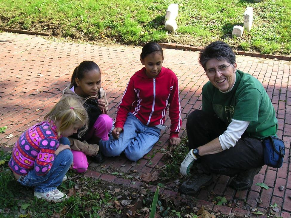 A woman gardens with three children